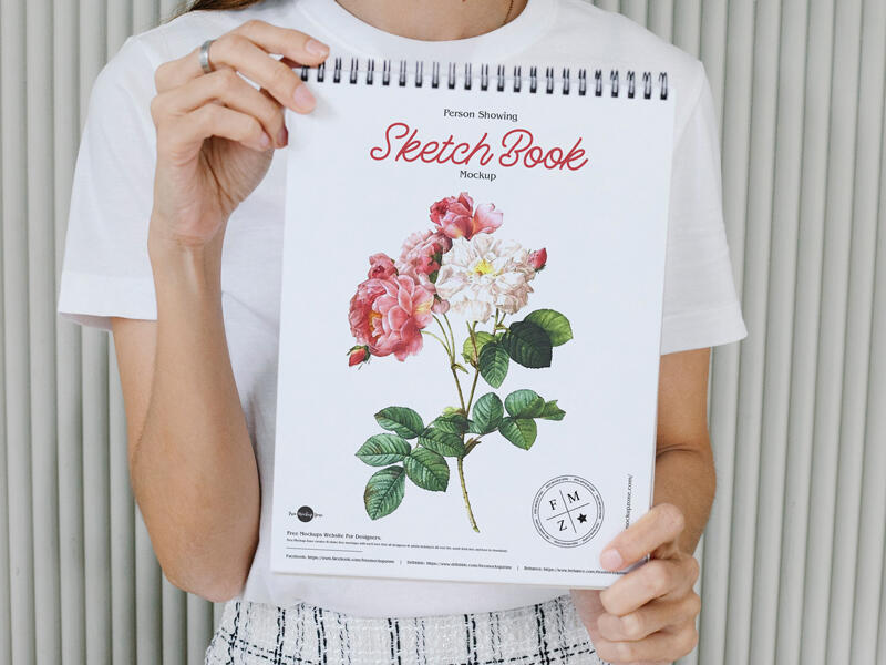 Free Person Showing Sketch Book Mockup PSD Template